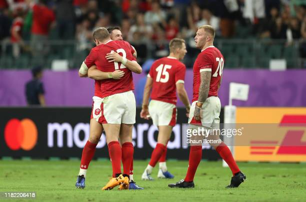 Hadleigh Parkes Owen Watkin and Ross Moriarty of Wales celebrate victory after the Rugby World Cup 2019 Quarter Final match between Wales and France...
