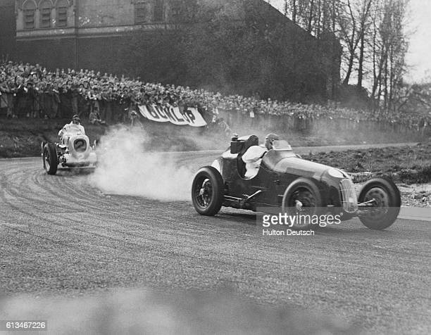 Hadley races in his Austin racecar in front of W.G. Everitt in his M.G. Racecar at the Coronation Trophy international race.
