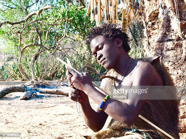 Hadzabe young bushman making the arrow for a hunting bow