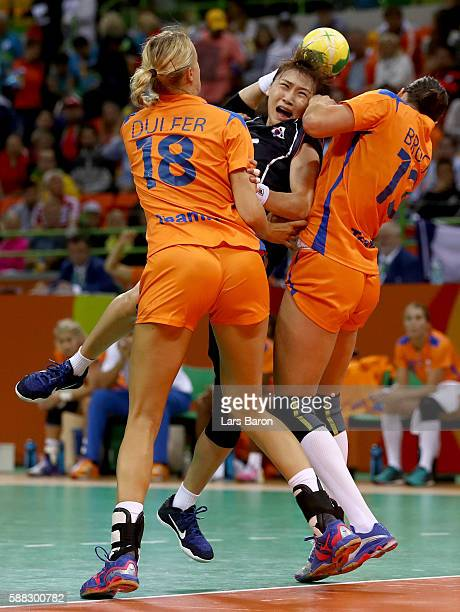 Haein Sim of Korea is challenged by Kelly Dulfer of Netherlands and Yvette Broch of Netherlands during the Womens Preliminary Group A match between...