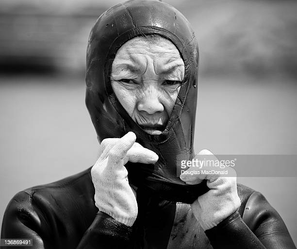 A Haenyeo starts to take off her mask at the 5th Haenyeo Diving Festival on Jeju Island South Korea