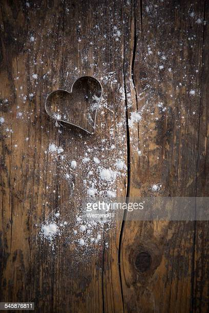 Haert shaped cookie cutter and scattered flour on dark wood