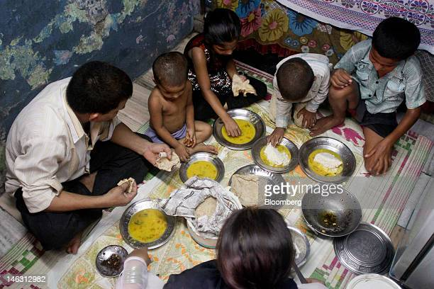 Hafiz Khan, left, eats lunch along with his wife, middle bottom, and four children in their rented home in the Dharavi slum area of Mumbai, India, on...
