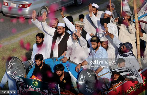 Hafiz Mohammad Saeed head of JamatudDawa waves to his supporters as he stands on a vehicle on the 16th anniversary of Pakistan's nuclear test on May...