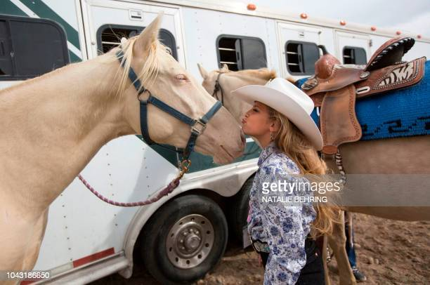 Hagann Gittins of Idaho Falls kisses her horse as she attends a Rodeo Queen Clinic in Rigby, Idaho, September 29, 2018. - The aspiring rodeo queens...