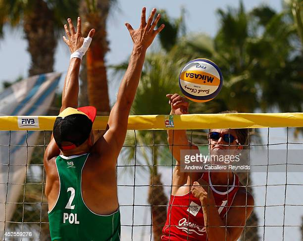 Hagen Smith from the USA spikes past Tomasz Wierzbicki from Poland at the FIVB Under 21 Beach Vollyball World Championships on July 23 2014 in...