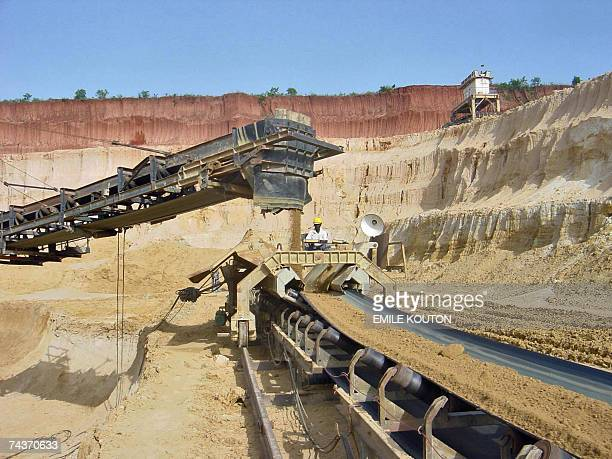 TO GO WITH AFP STORY BY EMILE KOUTON Picture taken 18 May 2007 shows workers standing past an old phosphate treatment caterpillar in Hahatoe 40 km in...