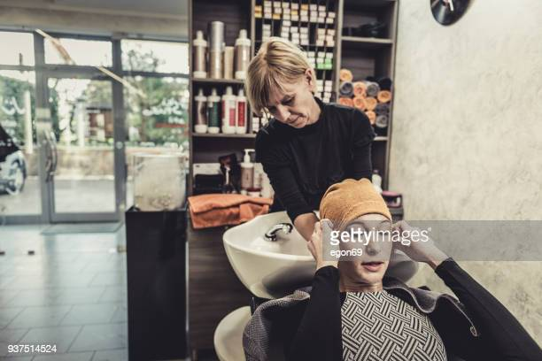 haidresser washing hair - hair conditioner stock photos and pictures