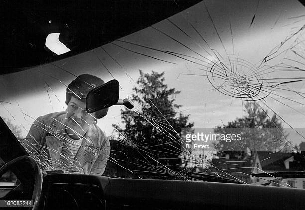 JUN 20 1977 Hail Damage Surveyed Betty Van Pelt Douglas County District Court clerk surveys shattered windshield of a car one of many damaged hail in...