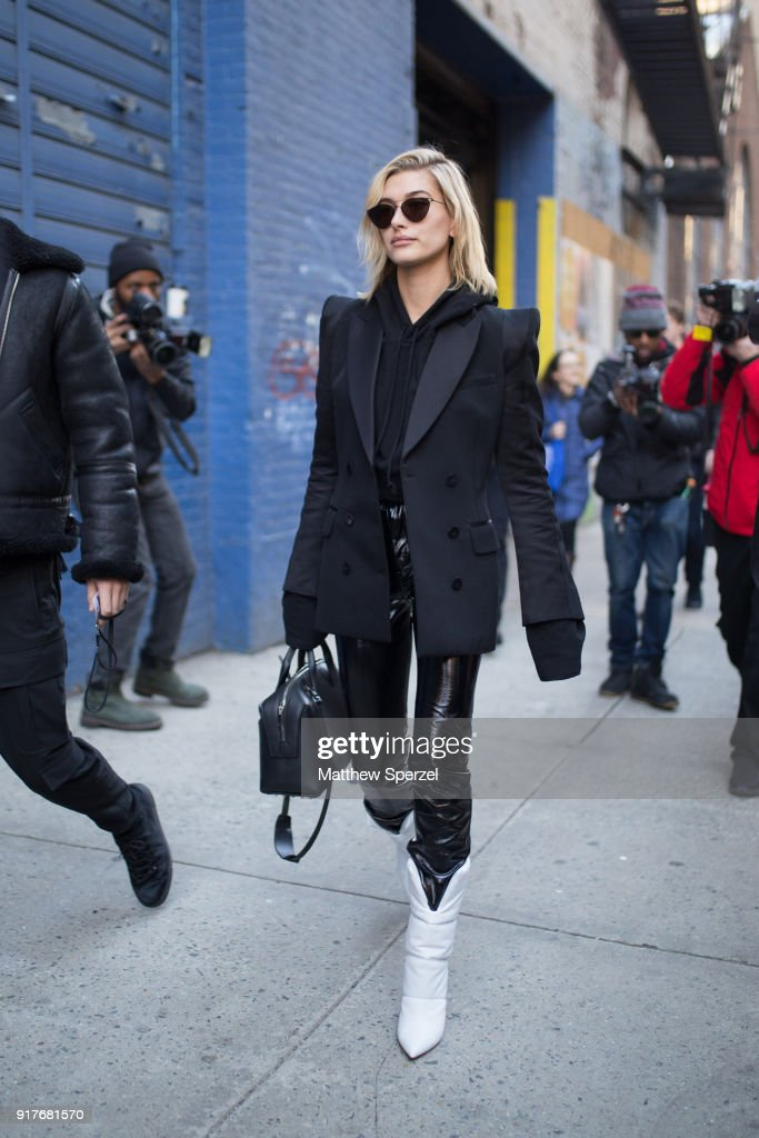Hailey Baldwin is seen on the street attending Zadig & Voltaire during New York Fashion Week wearing all-black with jacket, hoodie, and vinyl pants on February 12, 2018 in New York City.