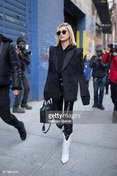 Hailey Baldwin is seen on the street attending Zadig & Voltaire during New York Fashion Week wearing all-black with jacket, hoodie, and vinyl pants...