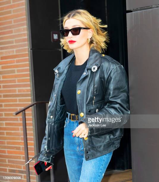 Hailey Baldwin wears a leather motorcycle jacket paired with denim jeans when heading out of her apartment on February 28 2020 in New York City