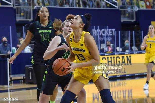 Hailey Brown of the Michigan Wolverines looks to shoot the ball while being guarded by Julia Ayrault of the Michigan State Spartans during the second...