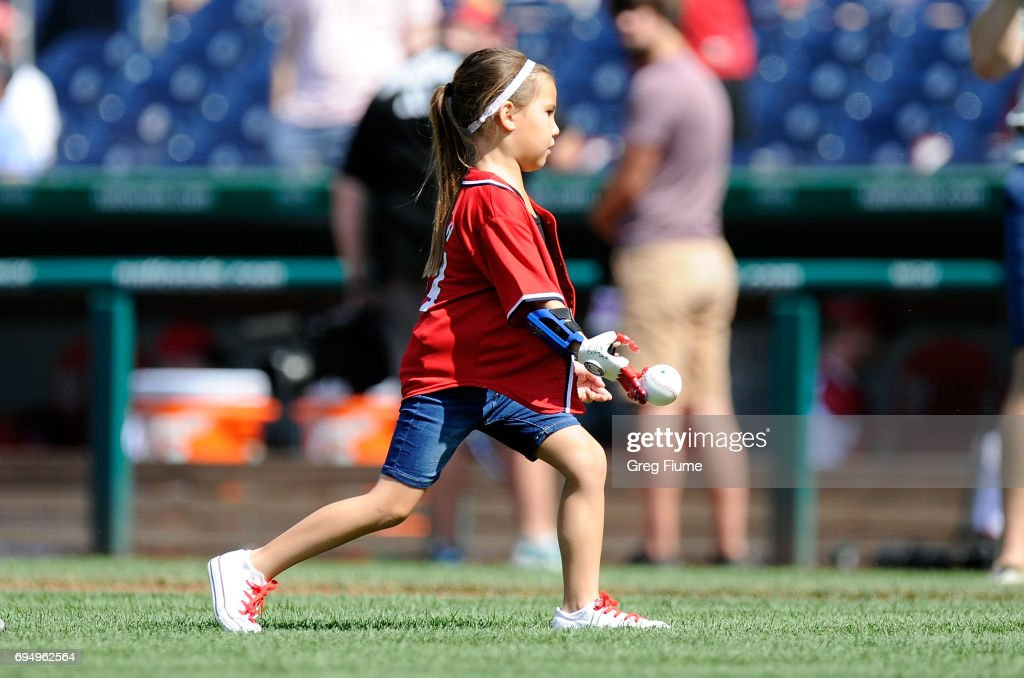 Hailey Dawson throws out the opening pitch with her 3D printed hand before the game between the Washington Nationals and the Texas Rangers at Nationals Park on June 11, 2017 in Washington, DC.