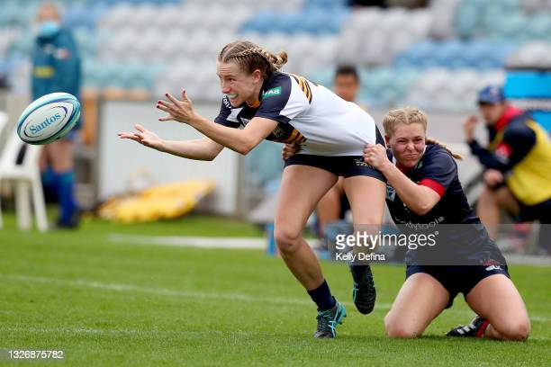 Hailey Derera of the Brumbies passes while being tackled Amy Williams of the Rebels during the Super W match between the Melbourne Rebels and the ACT...