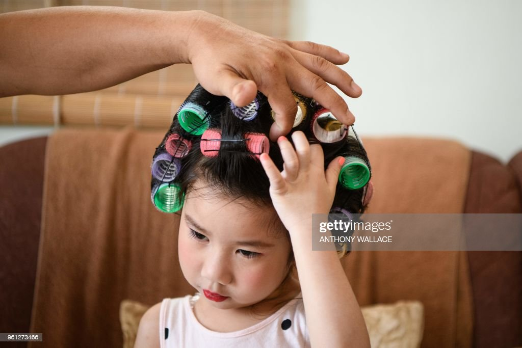 Hailey Miu, 4 years old, and her father soothe an itch on her scalp during preparations for her makeup and hair for her character as a landlady from Stephen Chow's movie 'Kung Fu Hustle' that she will portray during the annual Cheung Chau bun festival parade in Hong Kong on May 22, 2018.