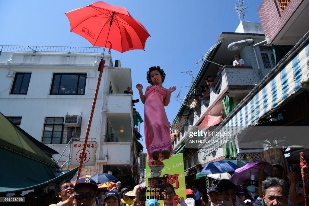 Hailey Miu (C), 4 years old, stands on a float while portraying a landlady from Stephen Chow's movie 'Kung Fu Hustle' during the annual Cheung Chau bun festival parade in Hong Kong on May 22, 2018.
