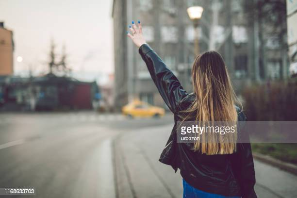 hailing a cab in the city - jacket stock pictures, royalty-free photos & images