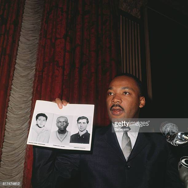 """Hails """"steps toward justice""""...Civil rights leader Dr. Martin Luther King holds up photos of the three young civil rights workers murdered in..."""