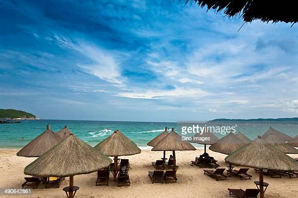 hainan, sanya, tourists lying in the deckchairs under parasol - hainan island stock pictures, royalty-free photos & images