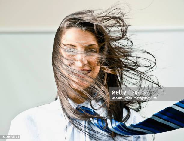 Hair and tie of Caucasian businesswoman blowing in wind