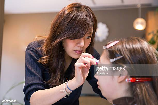 hair artist making up her client in hair salon - メイクアップ ストックフォトと画像