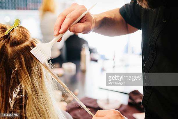 A hair colourist, a man using a paintbrush to cover sections of a womans blonde hair.