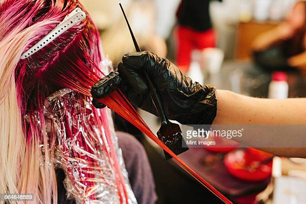 a hair colourist applying pink hair colour to a clients long blonde hair. - hair colourant stock pictures, royalty-free photos & images