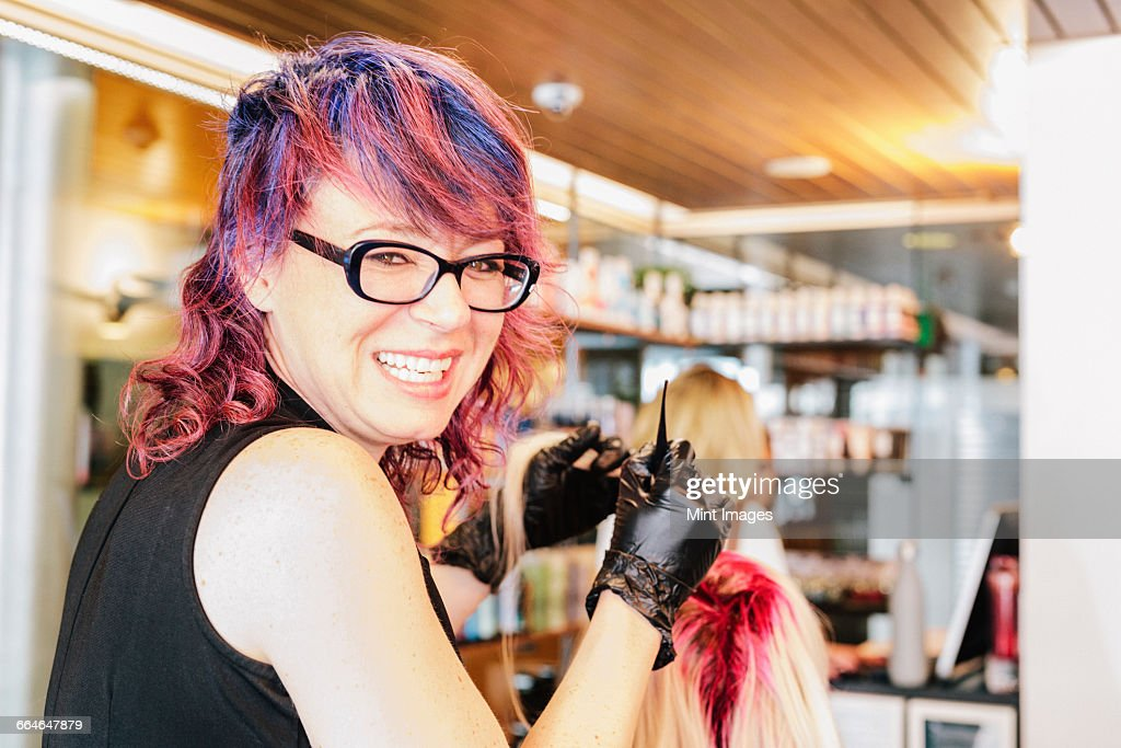 A Hair Colourist In Gloves Applying Red Hair Dye To A Clients Blonde