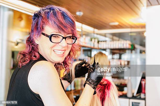 a hair colourist in gloves applying red hair dye to a clients blonde hair with a brush. - hair colourant stock pictures, royalty-free photos & images