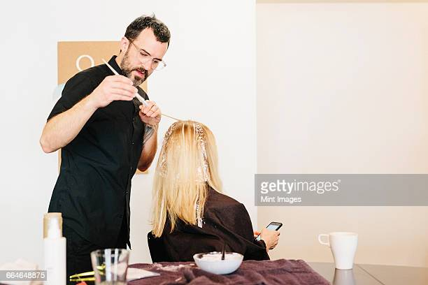 a hair colourist working with foils to give a client with long blonde hair highlights and lowlights using colour. - highlights stock pictures, royalty-free photos & images