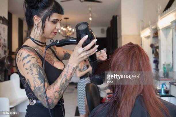 A hair dresser styling a customers hair.