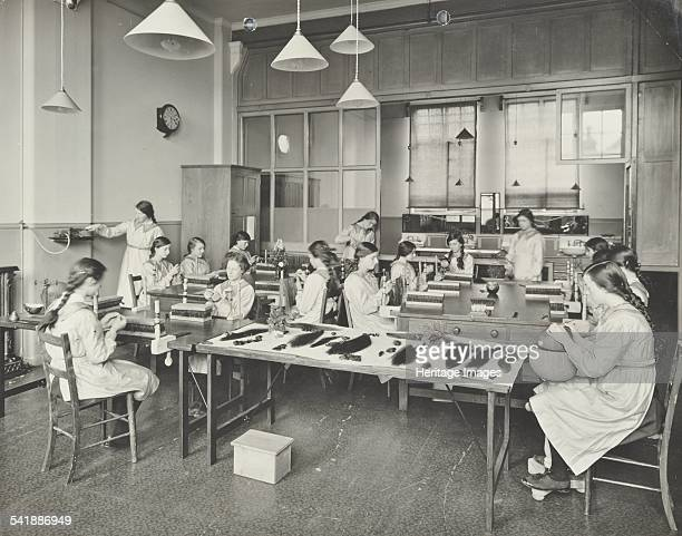 Hair dressing class Barrett Street Trade School for Girls London 1915 Bunches of hair can be seen on the table in the foreground for wig making...
