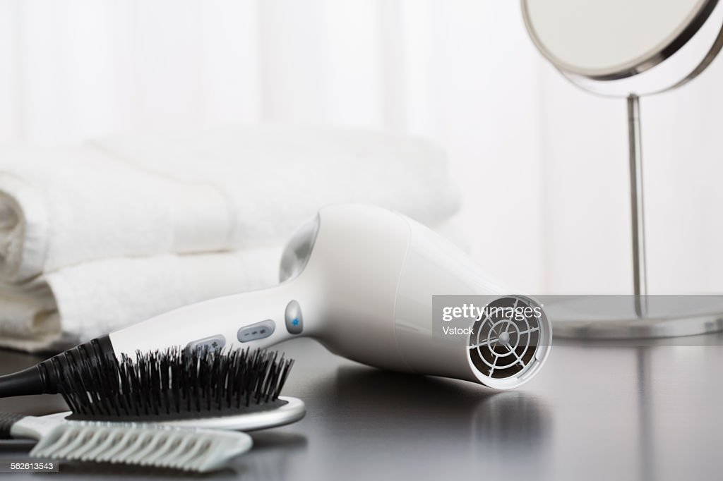 Hair dryer and towels on table : Stock Photo