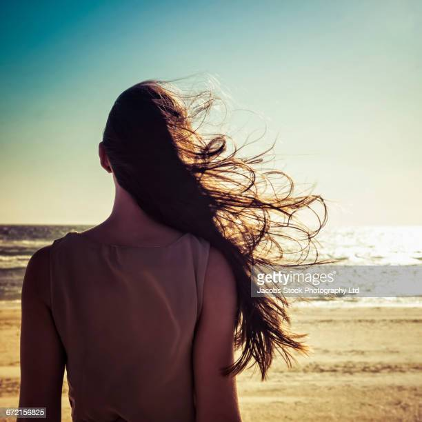 hair of caucasian woman blowing in wind at beach - blowing stock pictures, royalty-free photos & images