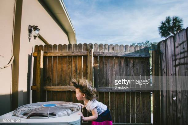 Hair of mixed race girl blowing from outdoor fan