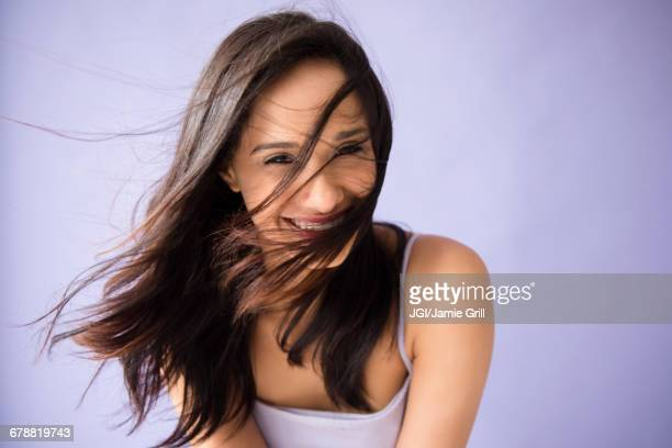 hair of mixed race woman blowing in wind - purple background stock photos and pictures