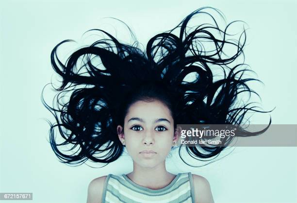 Hair of wide-eyed Mixed Race girl blowing
