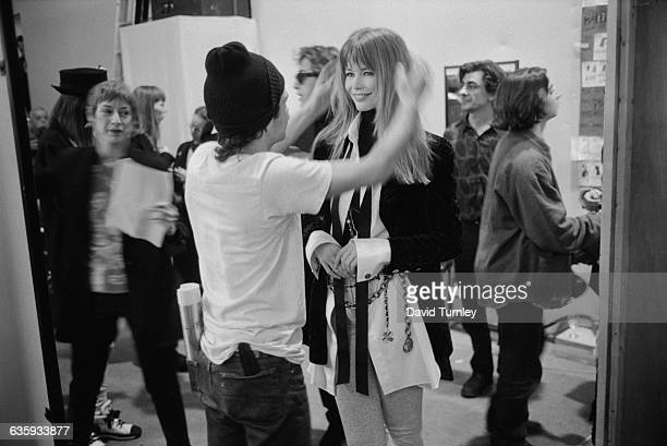 A hair stylist arranges Claudia Schiffer's hair before she models an outfit