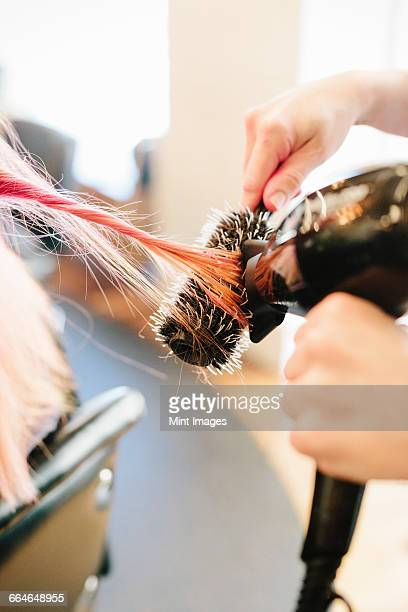 A hair stylist blow-drying a clients long straight pink hair using a round bristle brush.