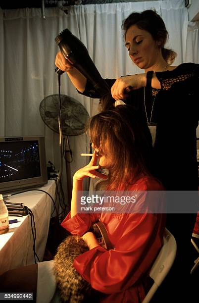 A hair stylist blows out the hair of one of the runway models at the 8th Annual Victoria's Secret Fashion Show minutes before the opening of the show...
