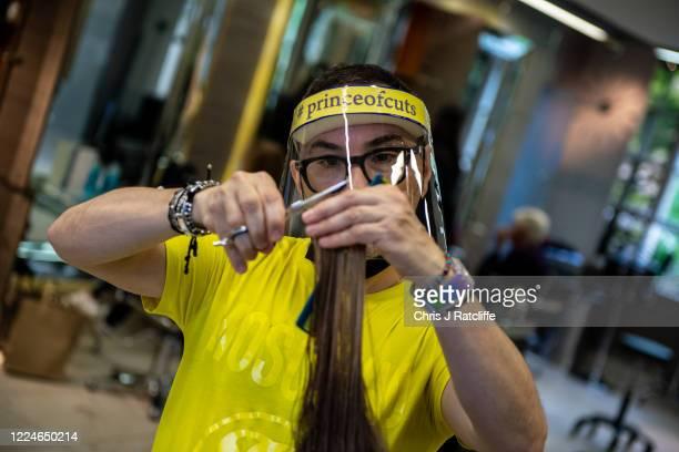 Hair stylist Cristiano Basciu wears a visor as he cuts Annethe Nathans hair at Richard Ward salon on July 4 2020 in London United Kingdom...