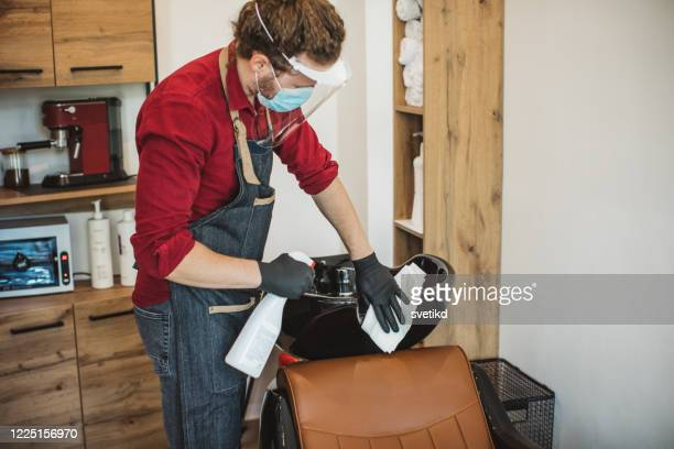 hair stylist disinfecting work space - hairdresser stock pictures, royalty-free photos & images