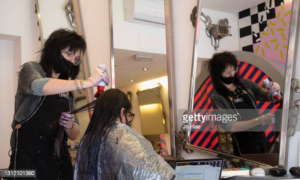 Hair Stylist Tommy D'Amour attends to his first client as Tusk Hair Salon re-opens in Camden High Street on April 12, 2021 in London, England....
