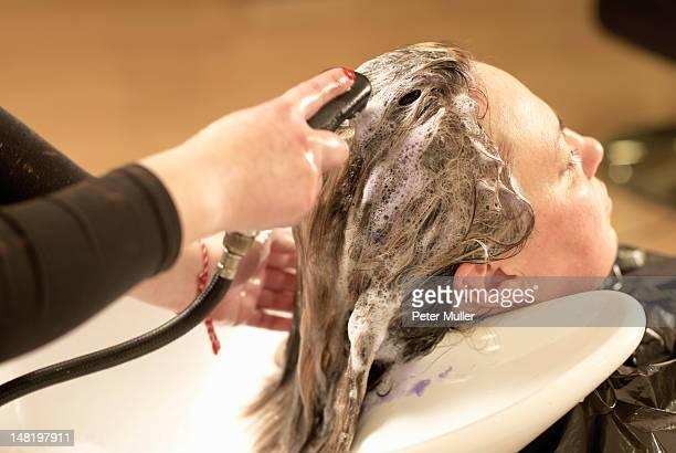 Hair stylist washing clients hair