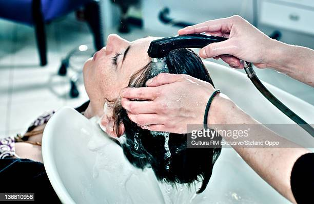 Hair stylist washing hair in salon