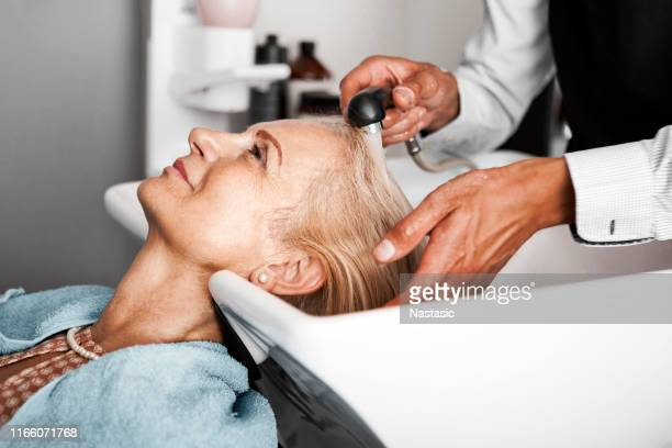 hair stylist washing mature woman hair - beauty salon stock pictures, royalty-free photos & images