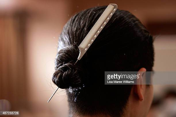 A hair stylist wears a comb in his hair backstage ahead of the LAMARCK show as part of Mercedes Benz Fashion Week TOKYO 2015 S/S at RISTORANTE ASO on...