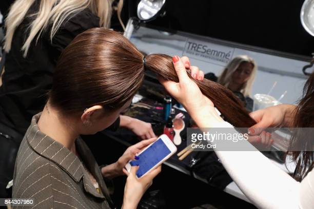 A hair stylist works backstage at the TRESemme at Cushnie et Ochs NYFW SS18 Backstage during New York Fashion Week at Skylight Clarkson Sq on...