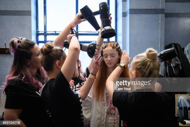 Hair stylists work on a model's hair ahead of a presentation by Haluminous at the Fashion Scout venue during London Fashion Week on February 19 2017...